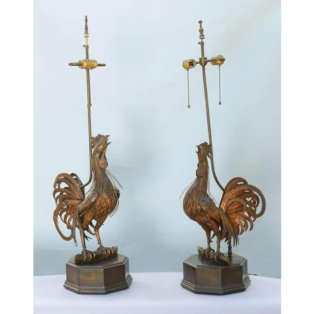 Unusual pair of lamps, of bronze, each fashioned as a well articulated rooster, perched upon a branch, raised on octagonal...