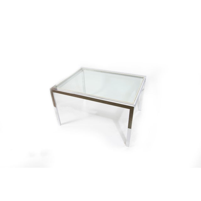 This beautiful modernist piece features nickel plating and supports two large glass table panes. The table is able to be...
