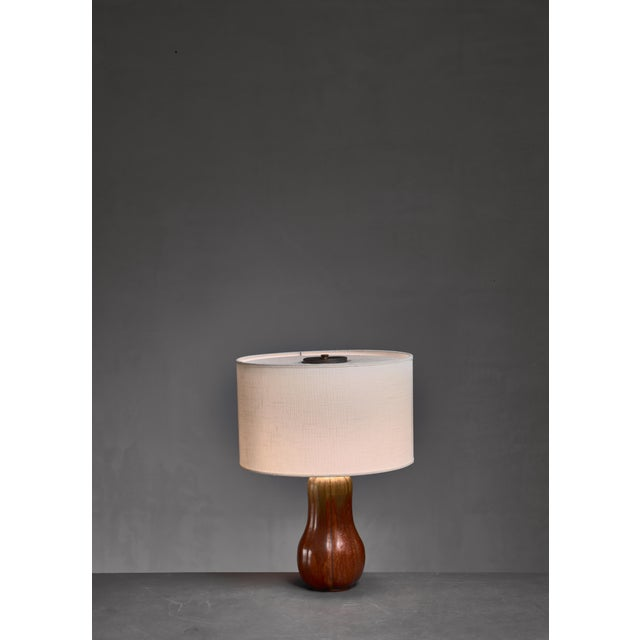 A ceramic table lamp with a brown and green glazing, by Arne Bang. Signed 'AB' and '49' underneath. The measurements...