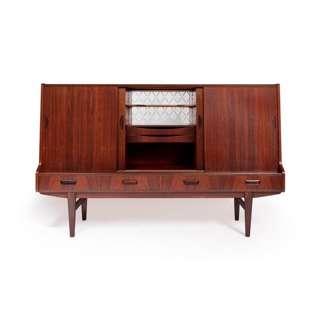 This beautifully crafted Danish modern mid century credenza in Brazilian rosewood showcases a gorgeous active grain...