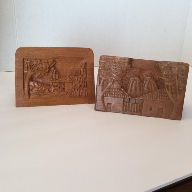 A pair of hand carved wood pen holders for your desk. Each one is unique. Both show detailed scenes of a home or houses,...