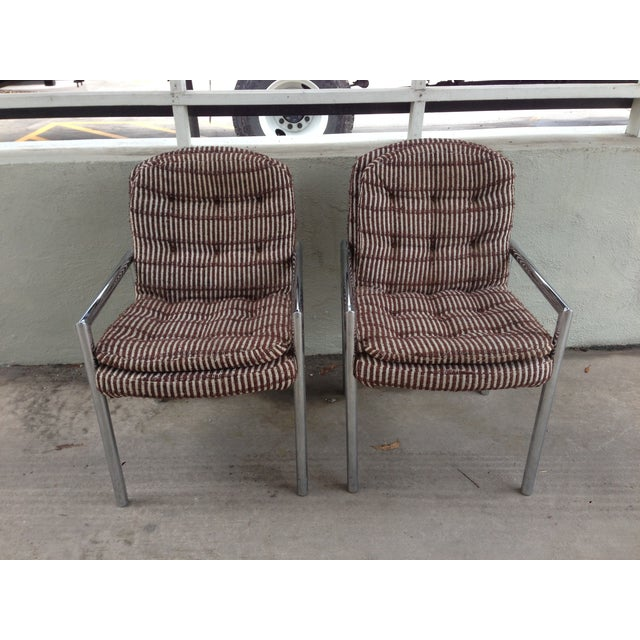A pair of Mid-Century chrome base upholstered armchairs in the manner of Milo Baughman. The chairs feature original fabric...