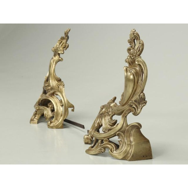 Antique French bronze andirons or chenets, done in a Rococo style from the late 1800s. There are no previous repairs and...