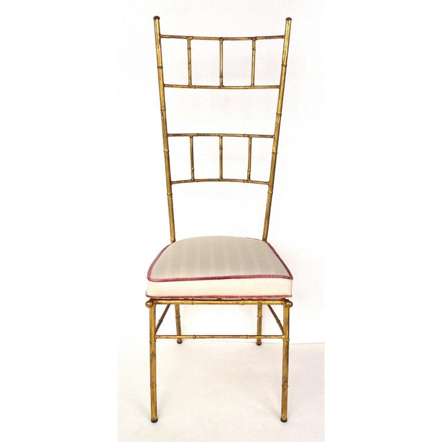 Stunning pair of vintage 1970's high-back faux bamboo Italian gilt-iron chairs created in the manner of Bagues. The chairs...