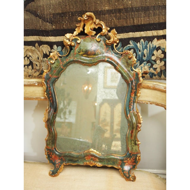 A 19th century or earlier Venetian rococo style mirror with an asymmetrical gilded crest over a cartouche with a decoupage...