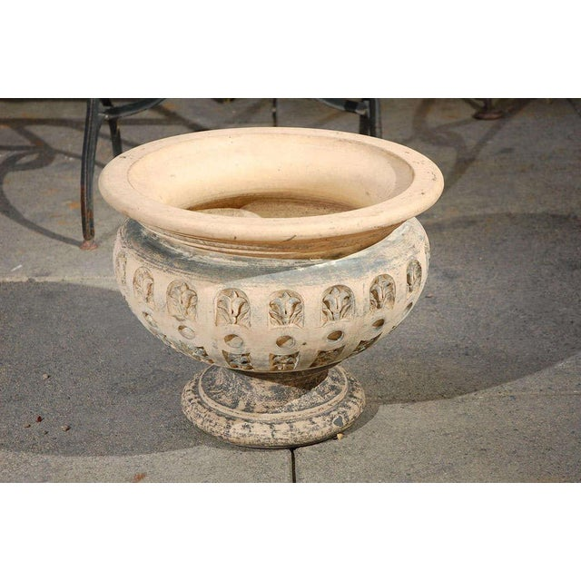 Elegant terra cotta planter with flared rim and fluted abstract flower motif from 19th century England. Used as a planter,...