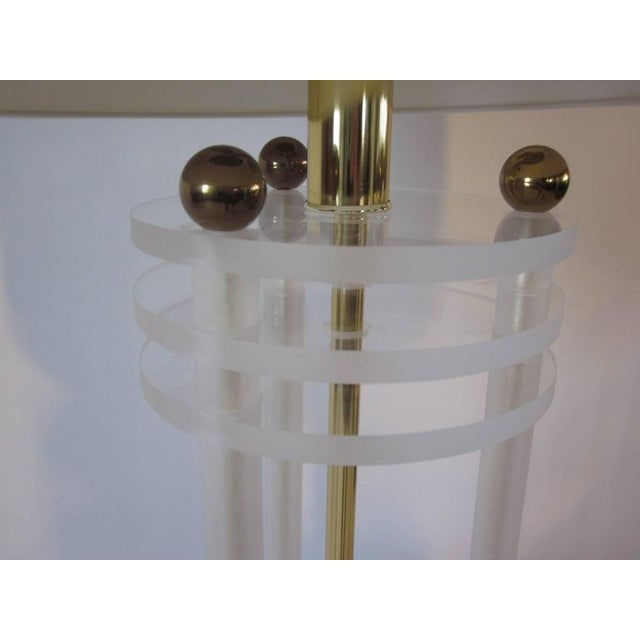 Columned Lucite table lamps with a mix of frosted and clear Lucite complemented with brass balls, rods and original finial...
