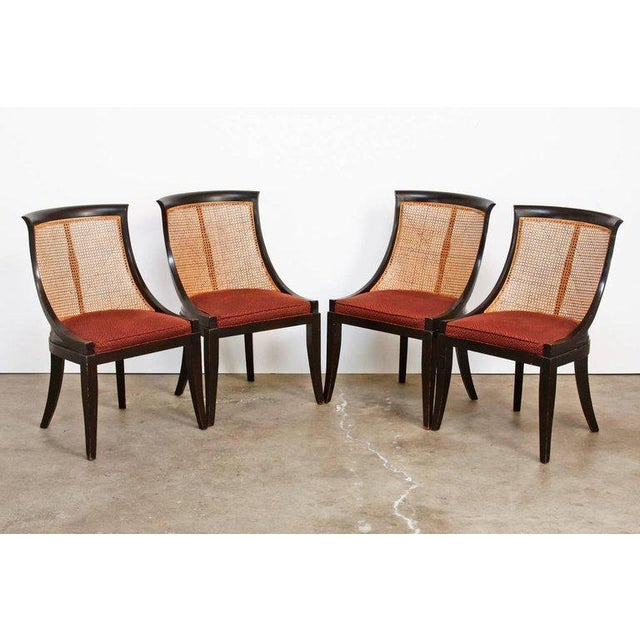Wicked set of four mid-century ebonized and caned dining chairs made in the manner of James Mont. The chairs have a scoop...
