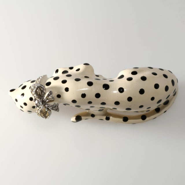Kenneth Jay Lane snow leopard brooch with pave' set clear rhinestoned bow around the neck. Eyes are green rhinestones....