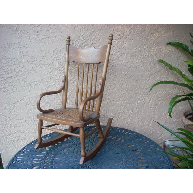An antique child's rocking chair with cane seat; traditional style with turned spindles and bent wood arms secured with...