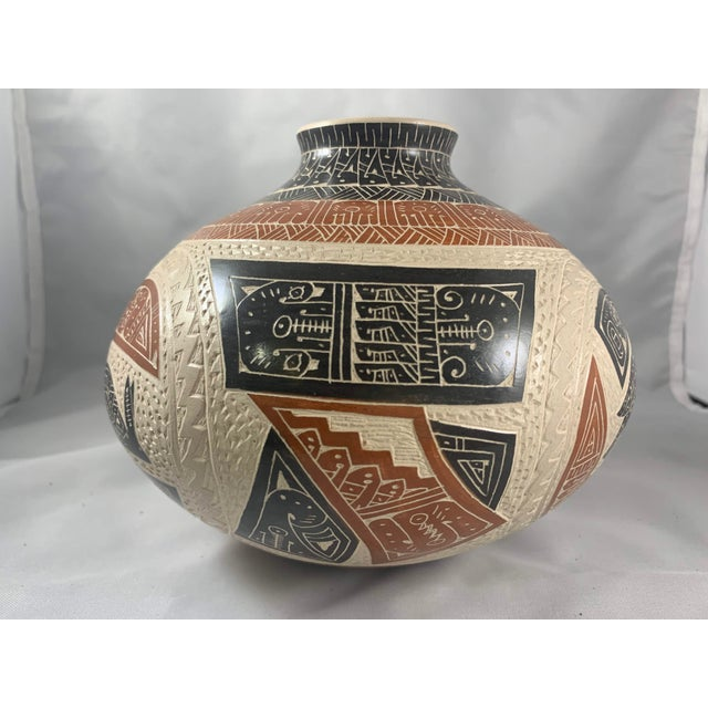 Fabulous narrow mouthed jar carved and painted with intricate detail. Signed by artist, Juan Carlos Rodriguez of Mata...