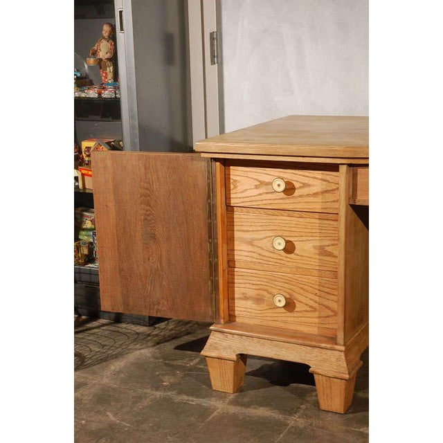 A good French early 20th century two pedestal oak desk crafted with dovetail joinery, applied moldings and paneled sides...