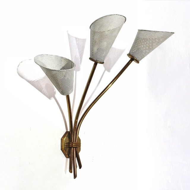 Three light sconce, brass and white lacquered perforated sheet metal or rigitule lampshades (in original condition). In...
