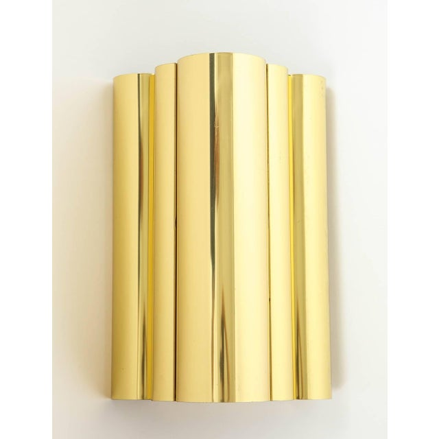 Pair of sleek brass sconces with a curvilinear form which gives an ambient glow when illuminated. Rewired for use in USA.