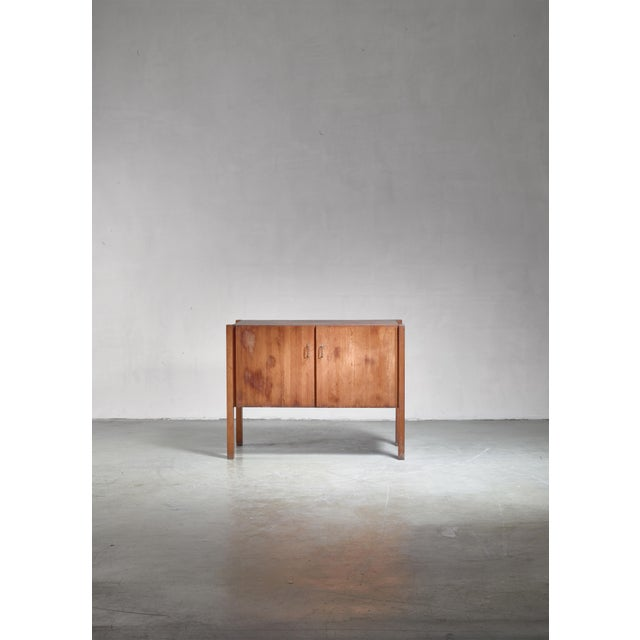 A Finnish pine sideboard with two doors with metal handles and two shelves inside, but more shelves can be added. Marked...