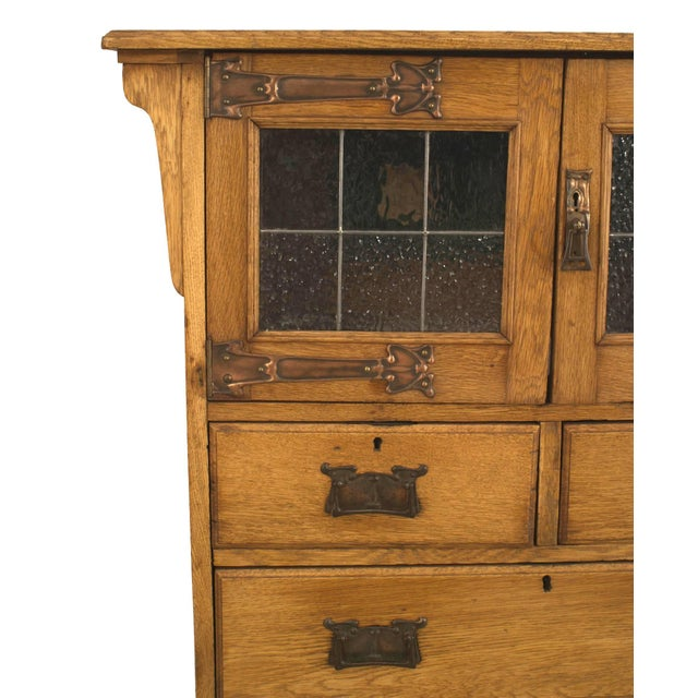 English Arts & Crafts oak cupboard cabinet with copper Art Nouveau hardware and two leaded glass doors.
