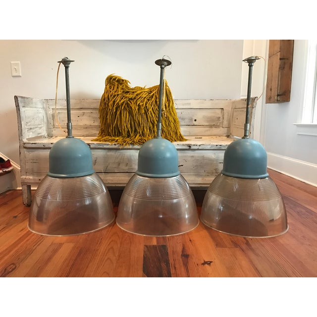"""These would look amazing over a kitchen island. The blue metal cap is a great coastal blue. The """"glass"""" is actually..."""
