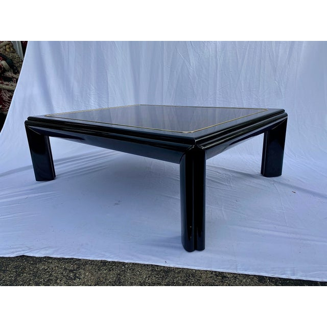 A monumental high gloss black lacquer coffee table with rich burl wood top outlined with a brass accent stripe. You will...