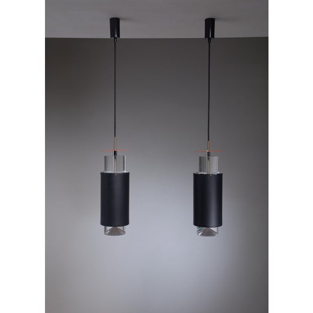 A pair of Simon Henningsen pendant lamps. The lamps have a black cylindrical metal shade with a plexiglass cylinder...