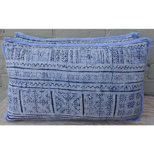 A pair of deep navy and soft blue patterned rectangular Batik pillows. Various square block designs appear on the front...