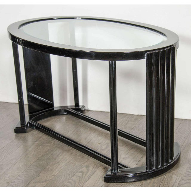 This oval form table features two supporting cross bars with two curved support legs with reeded design. This oval form...