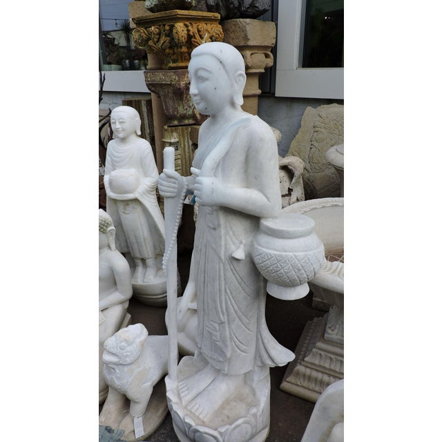 Solid white alabaster monk with walking cane and travel accessories.