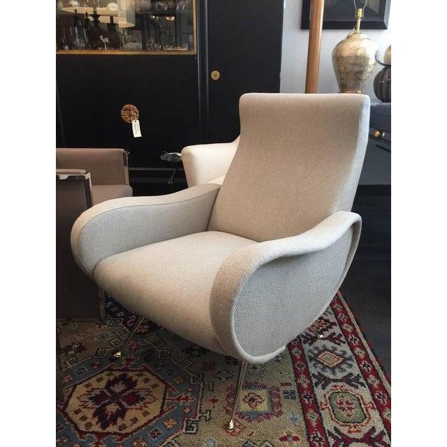 Polished brass feet and sculptural trim accents, finely upholstered.