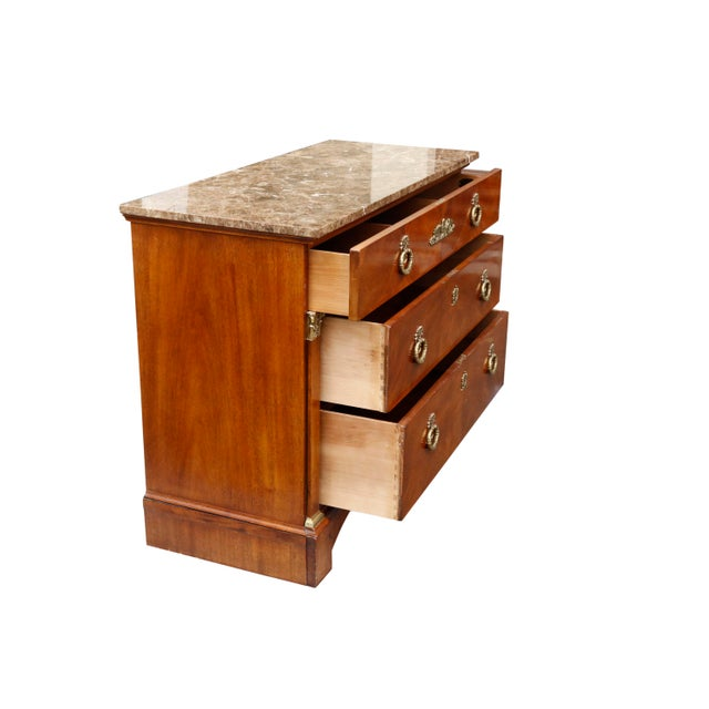 A French Empire style bonnet top chest made of cherry with a granite top. One over two dovetailed drawers are decorated...