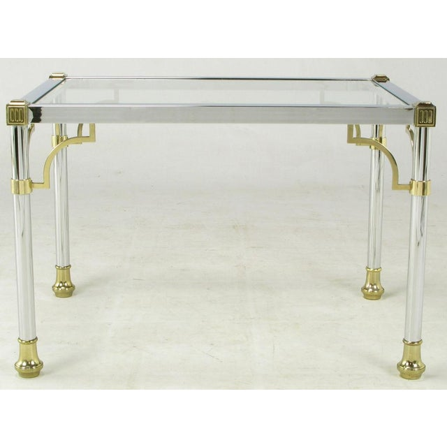 Chromed steel and solid brass side table, with clear glass top. Open brass brackets attached to every leg with brass...