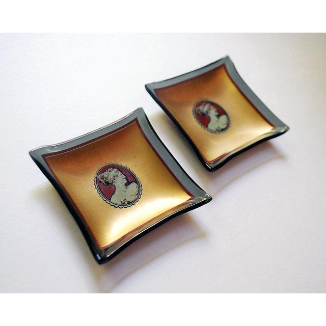Two marvelous vintage butter pat / serving dishes are made of black bent glass, printed on the top with a white cameo...