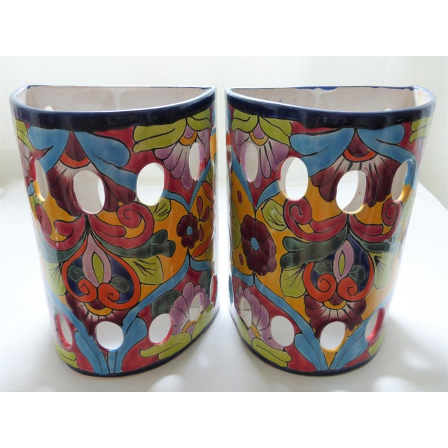 """A colorful pair of wall mounted ceramic lanterns, hand painted in Mexico in the style of Talavera pottery. With a 3.25""""..."""