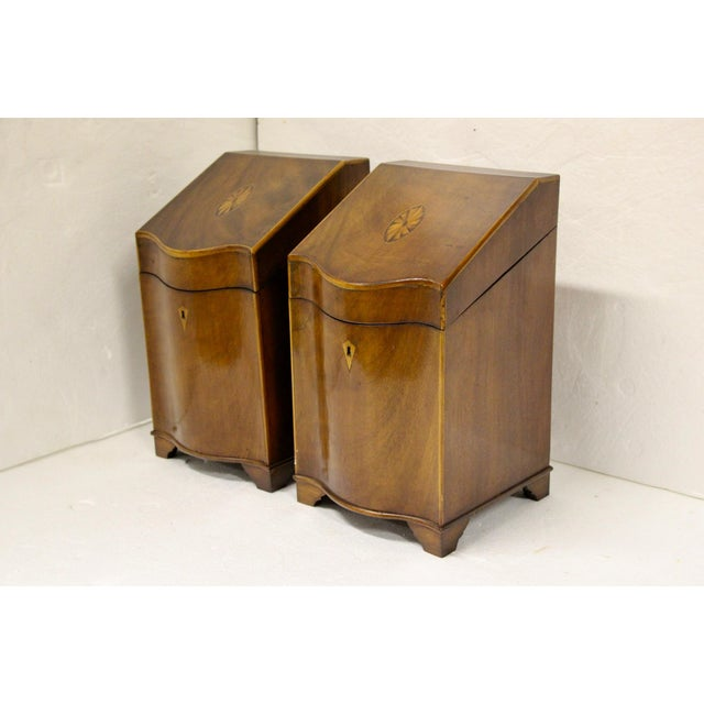 Handsome pair of English Georgian cutlery boxes. Serpentine fronts and sloped lids. Gorgeous pinwheel veneered cartouche...