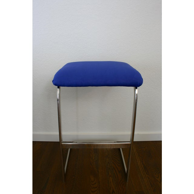 A pair of silver cantilever barstools with a royal blue faux suede fabric upholstered seat.