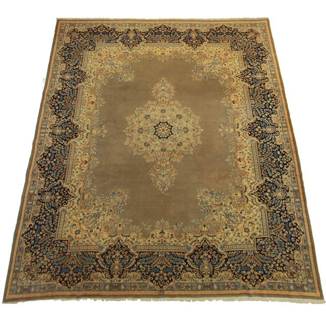 This Persian Kerman rug is a lovely brown/tan color. Made of hand-knotted wool.