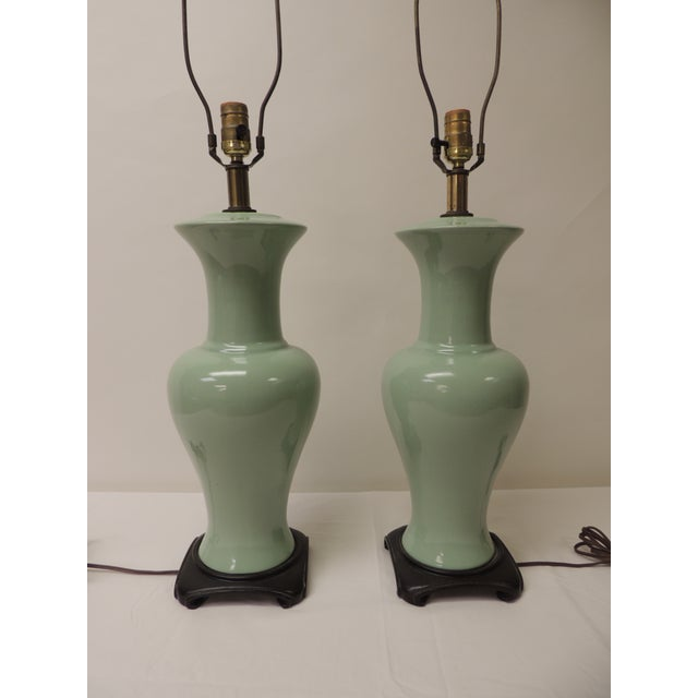 Requires (2) boxes for shipping. Pair of Vintage Celadon green Porcelain Table Lamps with rosewood bases and turned wood...