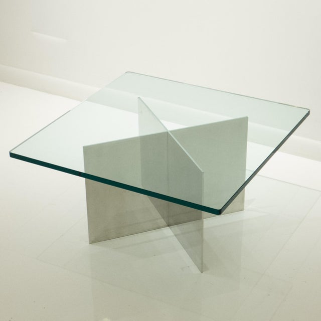 X-base cocktail or side table of two intersecting planes of highly polished cast aluminum, with a tinted 3/4 inch glass...