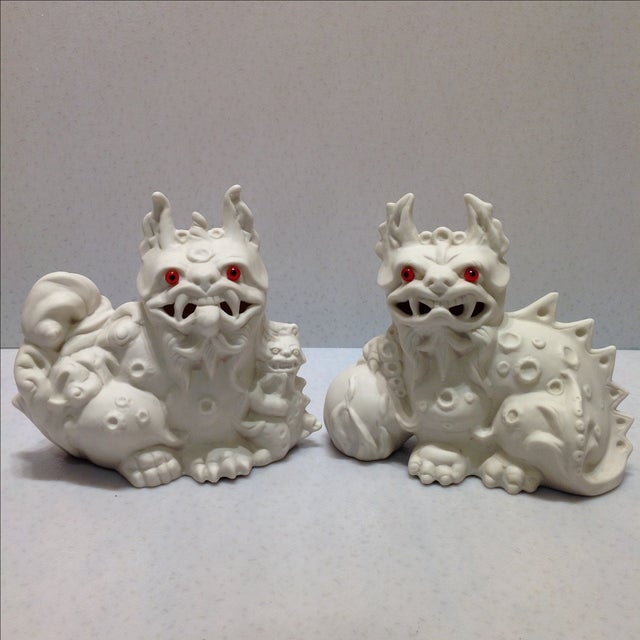 Offered is a pair of signed studio white porcelain foo dogs with red glass eyes. The foo dog with the egg has a stress...