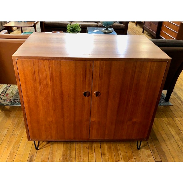 Exceptionally made Teak Danish Cabinet from the 1960's. Brass hardware for door hinges, new black iron hairpin legs have...
