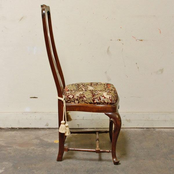 A vintage Queen Anne style fiddle back side chair. This mahogany chair features an arched crest rail above a shaped back...