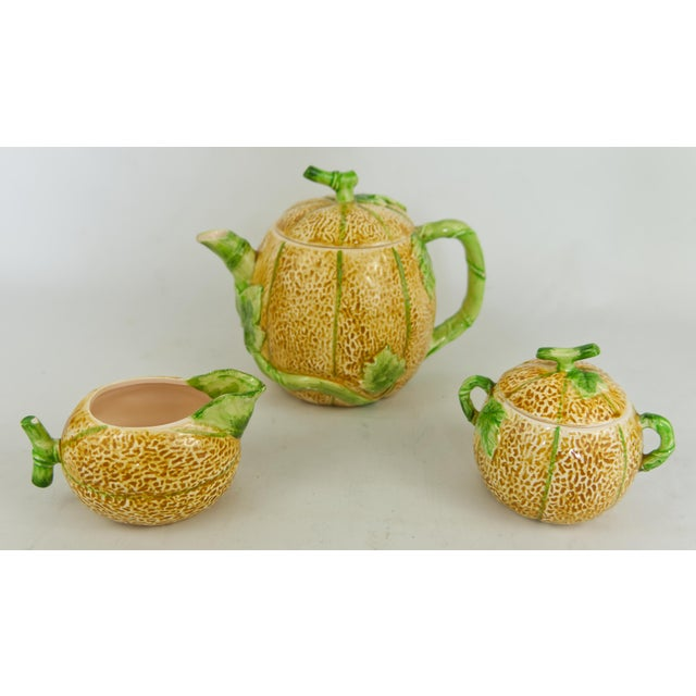 A 1982 ceramic cantaloupe melon shaped tea set including a creamer, teapot and sugar bowl with detailed texture and...