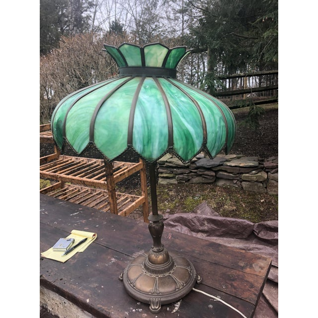 A very large antique leaded glass and brass table lamp having a luminous striking shade in various shades of green....
