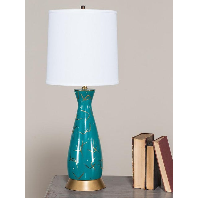 This hand painted vintage ceramic lamp from the Atomic Age in America circa 1950 has a whimsical presence. The shaped vase...