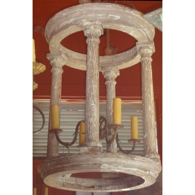 """The 4 wooden columns rest on a plinth. 25.5"""" bottom diameter. 4 cluster light on iron shaft. US Wired. Iron crown with 4..."""