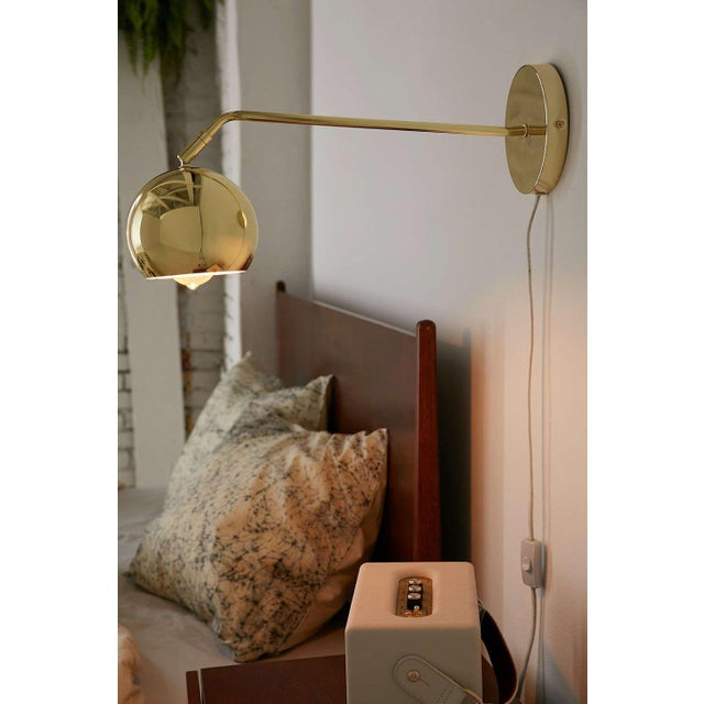 This set of two mid century wall lamps is a nice and stylish option for your home. Each lamp comes in a warm brass finish...
