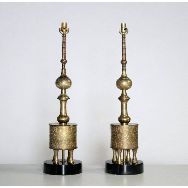 Midcentury table lamps in the manner of James Mont made of decorative brass on black round plinths topped with new custom...