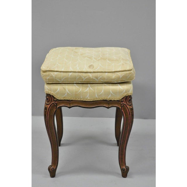 This is a vintage French Louis XV provincial style upholstered stool from the mid 20th century. It features pink painted...