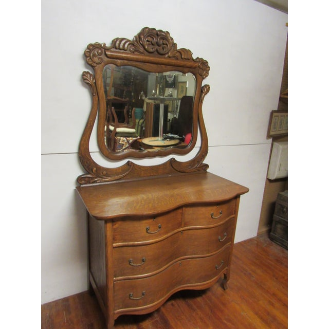 Turn of the century tiger oak radical serpentine dresser with beveled mirror and carved harp, four drawers. 44 x 21 x 34:,...