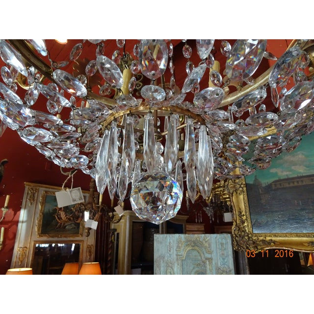 Bronze and crystal chandelier with 8 lights. Each arm has an acanthus motif with one single crystal pendant. Crystal ball...
