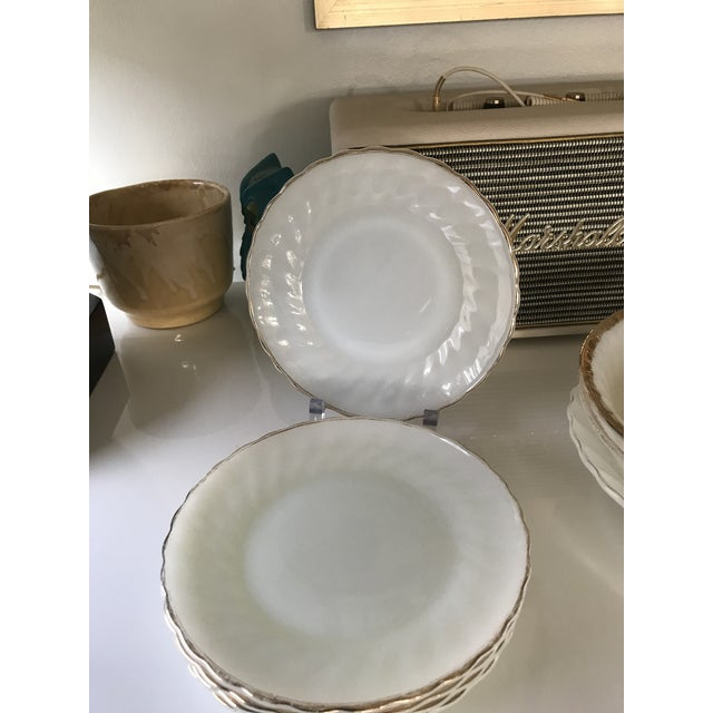 Eight pieces of Anchor Hocking suburbia Dinnerware. These milk glass pieces have a wavy fluted edge adorned with 22kt...