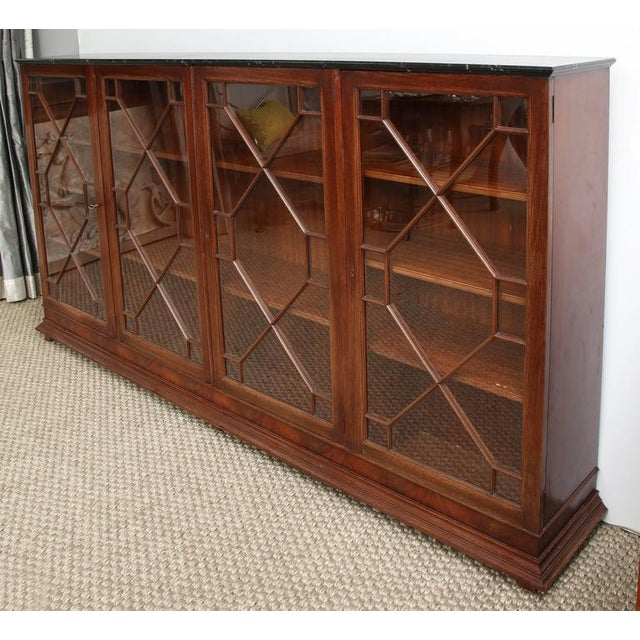 A handsome and versatile Chippendale style bookcase with four glazed doors, with glass inset in molded carving. The bottom...